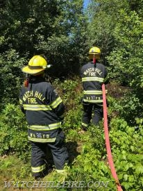 Firefighters Pat Majeika and Rachel Schilke advance a hose line deeper into the woods to extinguish the remnants of a small brush fire off Turtleback Road