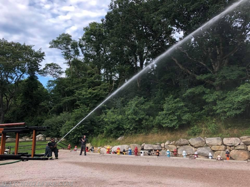 Lieutenant Chris Koretski and Firefighter Keith Maine display an antique nozzle and just how much water and reach can be achieved using them as they would have in 1917.