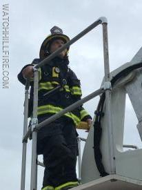 Firefighter Elterich assists in guiding the aerial ladder into position to check the roof at 3 Lighthouse Road