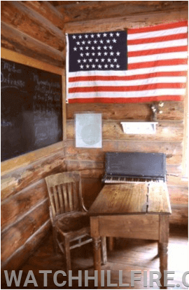A old historical view of a small one room schoolhouse displaying the United States Flag.