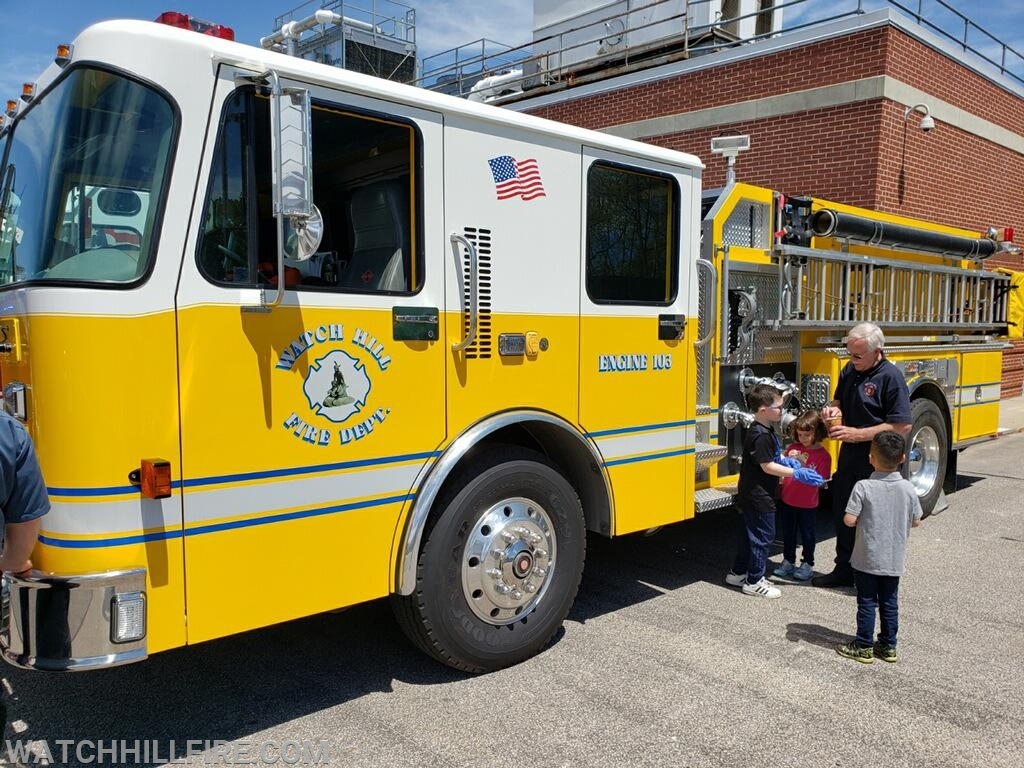 Firefighter Bob Perkins provides young visitors with a tour of Watch Hill Engine 103