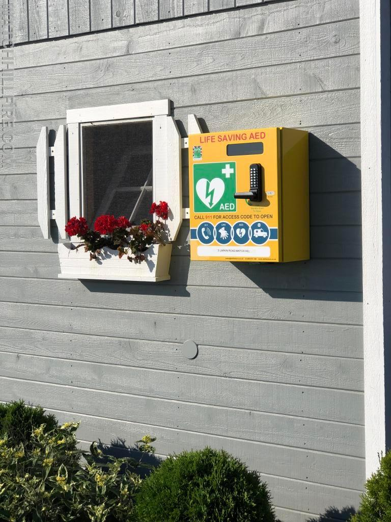 The new AED and Access Security Box at the Watch Hill Fire District Larkin Road Parking Lot Booth by the Larkin Road Public Bathrooms.