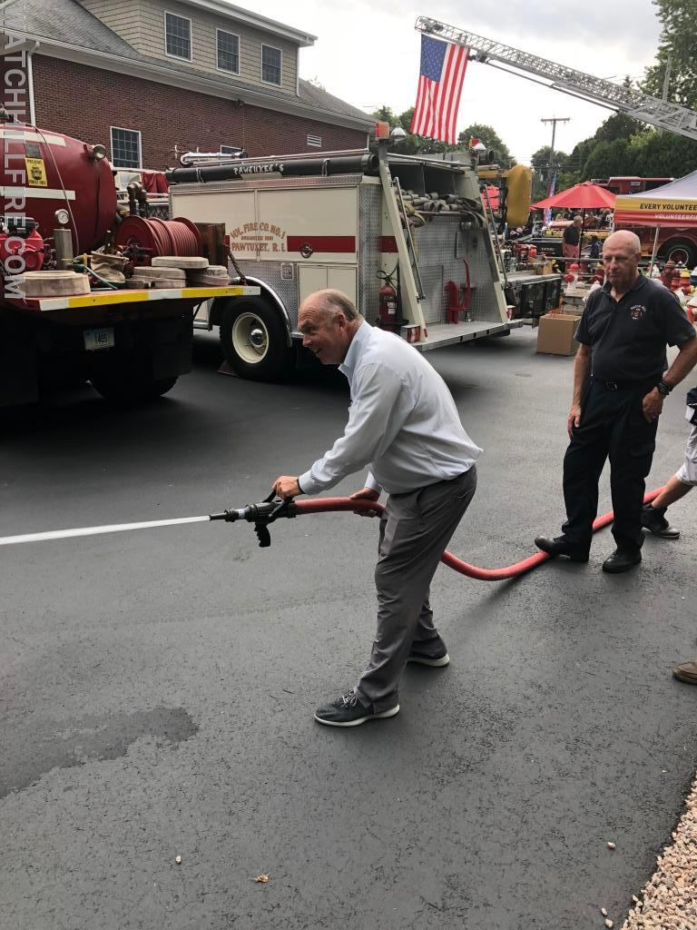 Phil Koretski, father of Lieutenant Koretski shoots the hose with help from Lieutenant Davis