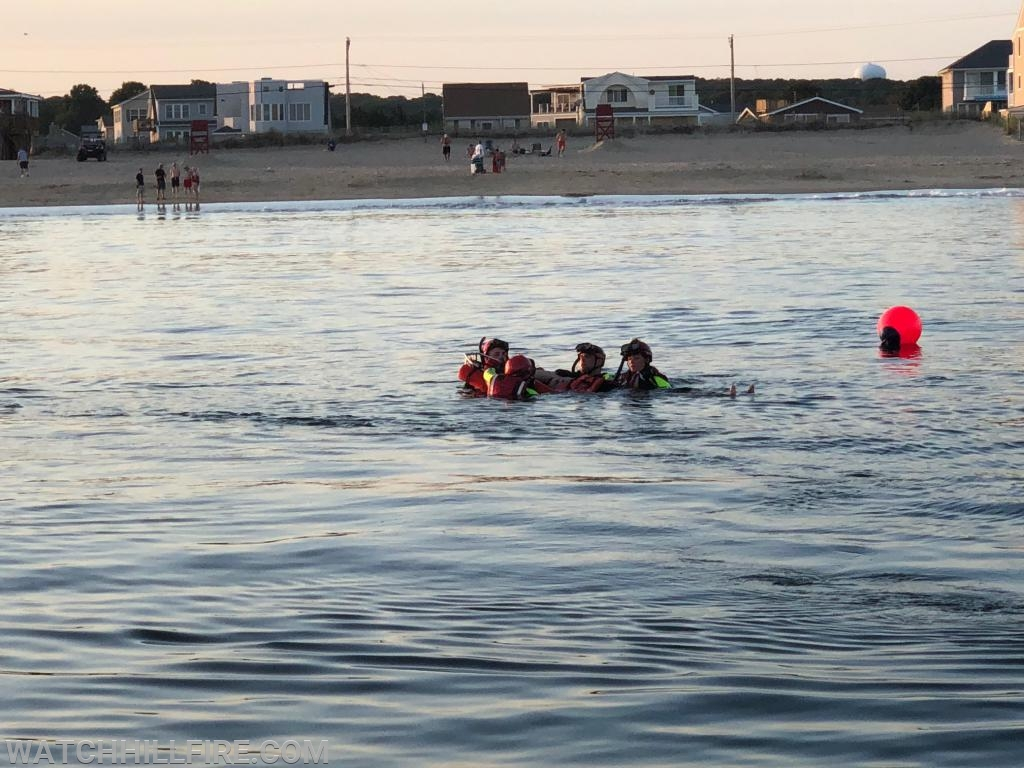 Charlestown Rescue Swimmers Deputy Chief Chris Wells, Lieutenant Jill Gardell, EMT Hannah Schilke, and Member Josh Gabriel package the victim in the floating stokes basket.