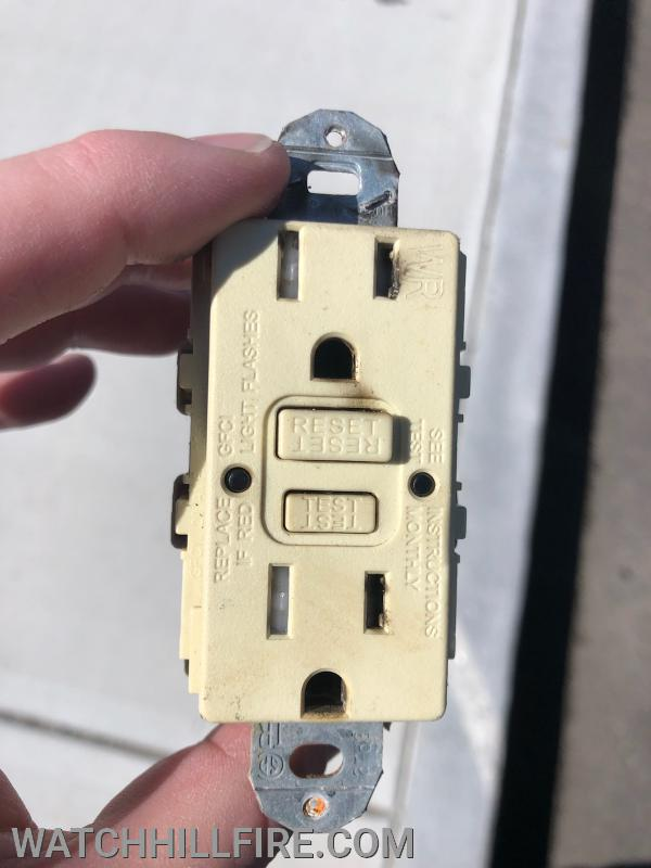 This outlet malfunctioned and began to smoke after a slight burning smell had been noticed earlier in the day.   The front view shows minimal discoloring and soot stains.