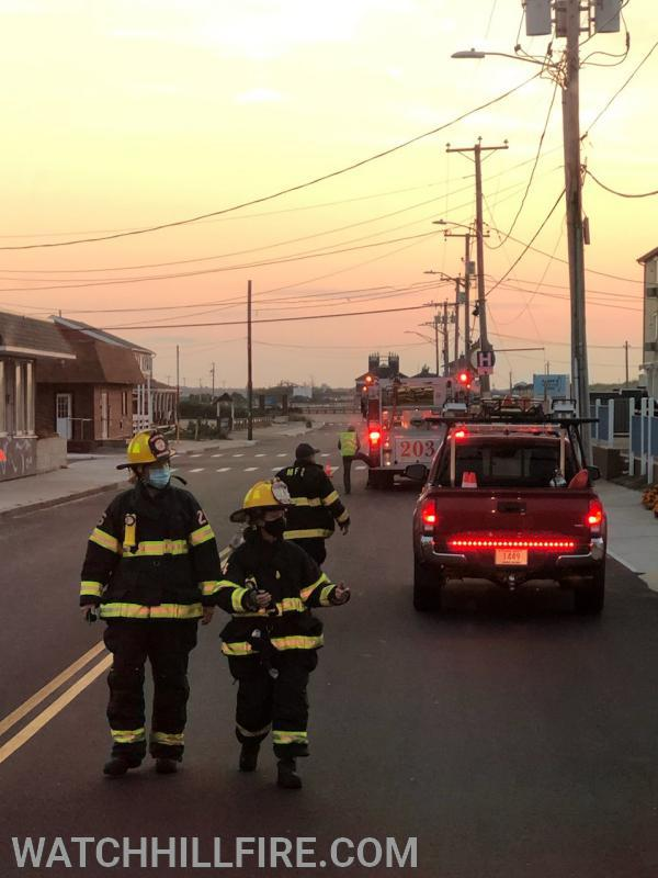 Watch Hill Captain Perkins and Watch Hill Firefighter Wood return to Ladder 104 after checking in with Misquamicut Firefighter Turnberg at the scene of an early morning mutual aid response with Watch Hill Ladder 104 to a three story hotel on Atlantic Avenue in Misquamicut.