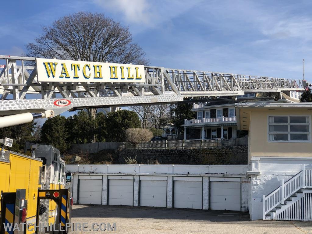 Ladder 104 reaches the corner of a flat roof on one of the buildings located in the Watch Hill Motor Court Complex