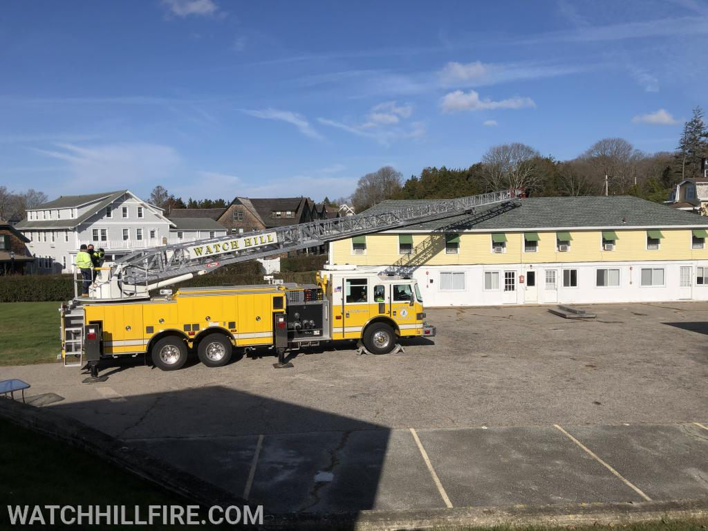 Ladder 104 reaches the middle of a peaked roof on one of the buildings located in the Watch Hill Motor Court Complex