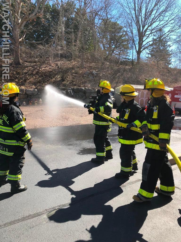 Firefighter Julie Wood and Firefighter Lauren Wilks assist with maneuvering a hose line while Captain Jane Perkins provides instruction.