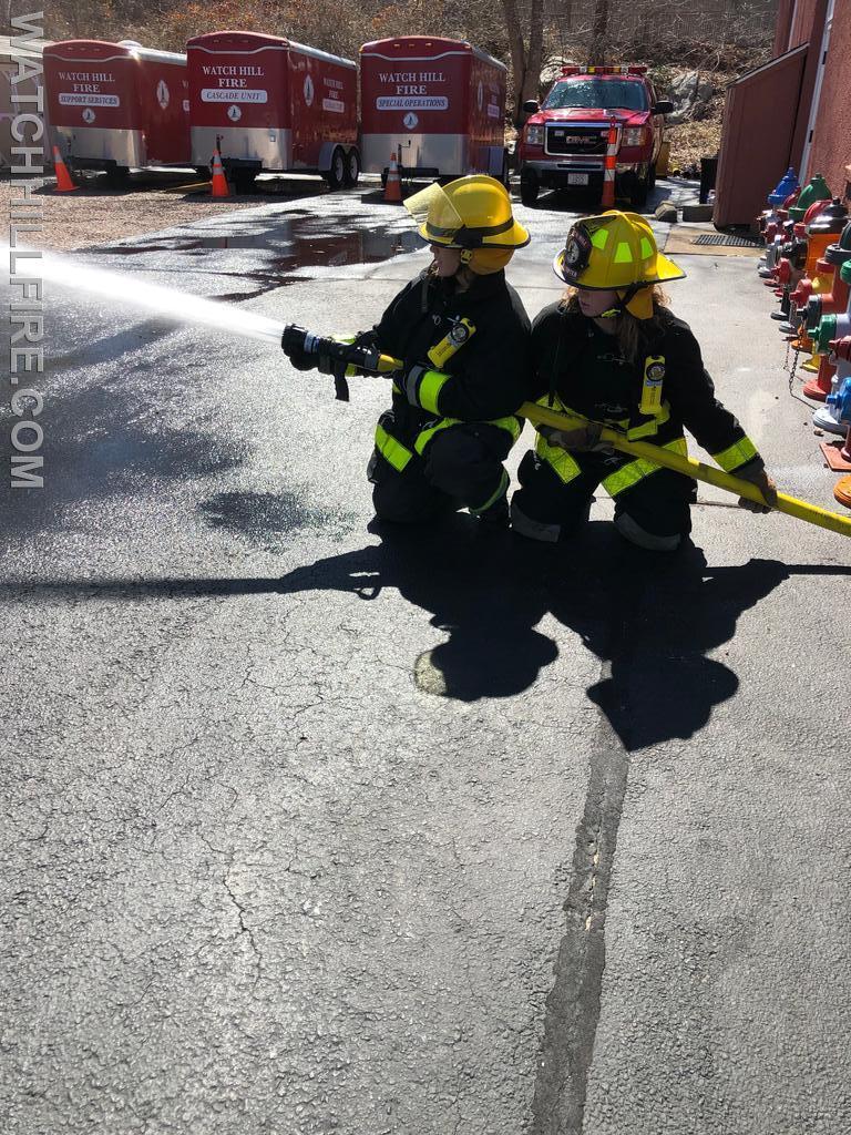 Firefighter Lauren Wilks and Firefighter Julie Wood practice maneuvering a hose line.