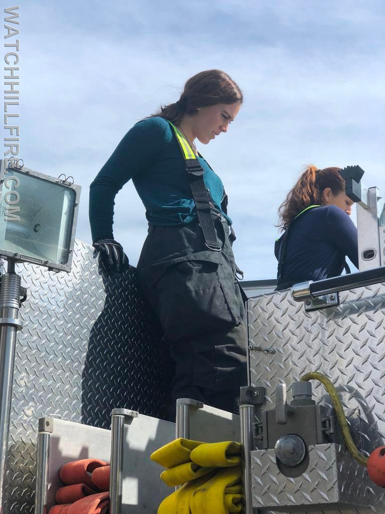 Firefighter Lauren Wilks and Captain Jane Perkins packing hose after a training session.