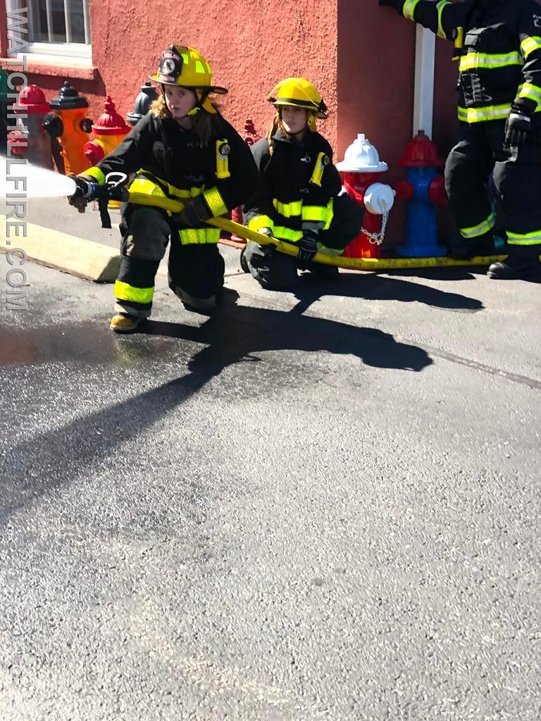 Firefighter Julie Wood and Firefighter Lauren Wilks practice maneuvering a hose line.