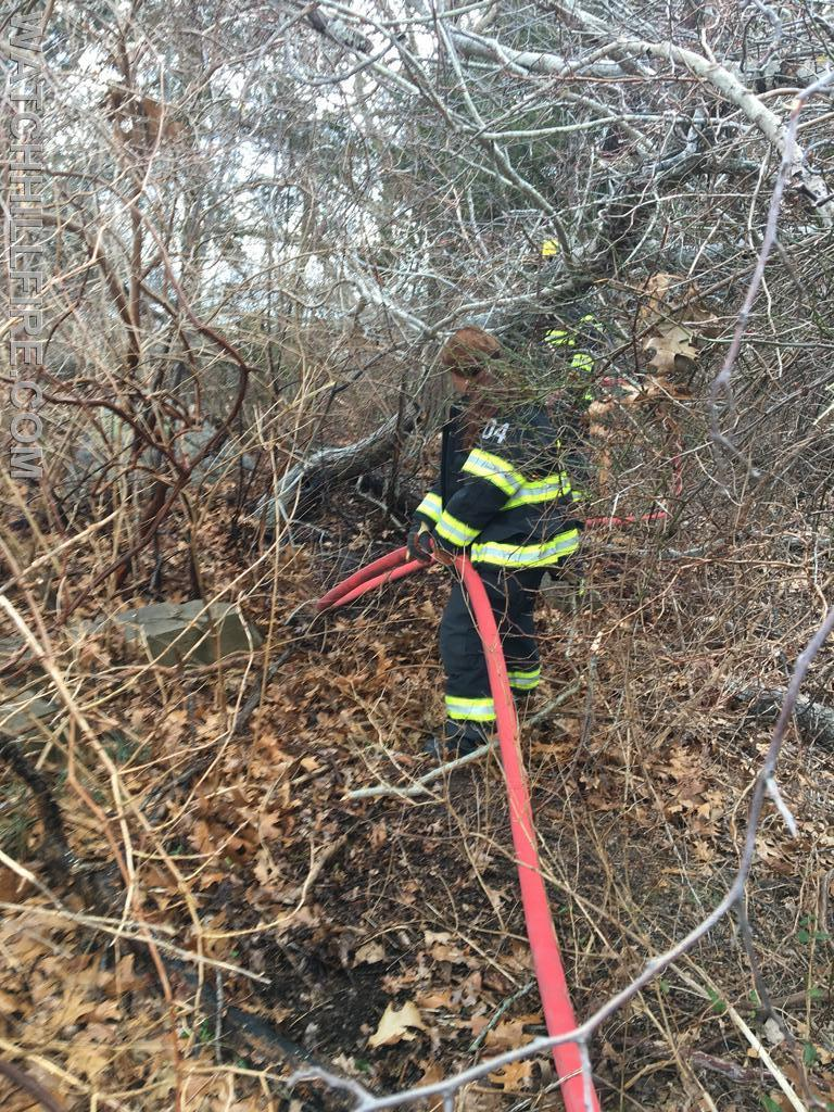 Captain Jane Perkins hauls hose out of the woods after a recent brush fire.