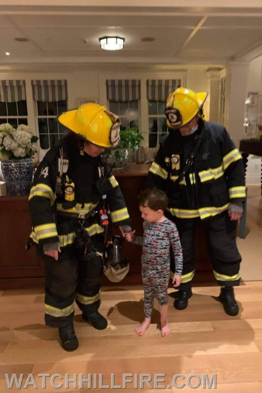 Captain Jane Perkins and Firefighter Dennis Evans with a young visitor from Maryland who apparently was enjoying being awake in the middle of the night!
