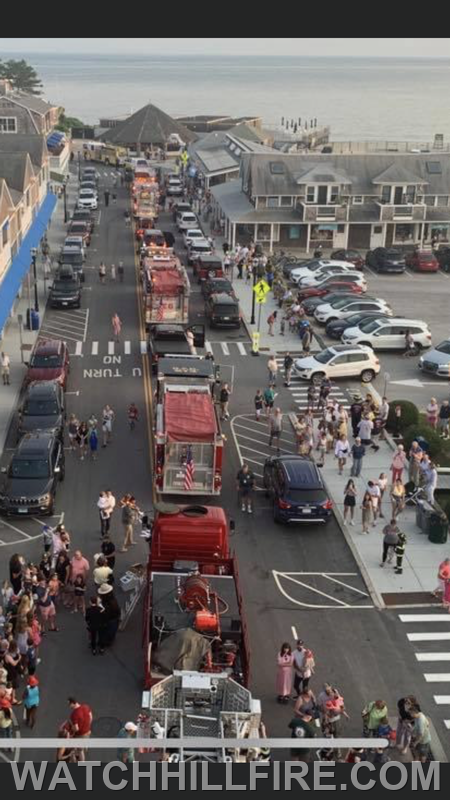 Twenty eight Fire and Rescue trucks were parked along Bay Street at the last stop of the parade. Smokey can be seen in the lower right interacting with the children. Photo complements of Hope Valley Fire.