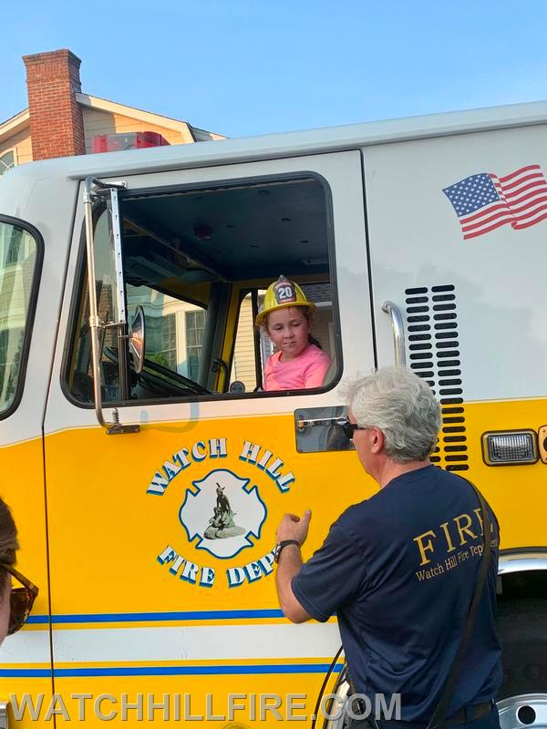 A child has their pictures taken while exploring Engine 103 at the second stop of the parade in Weekapaug