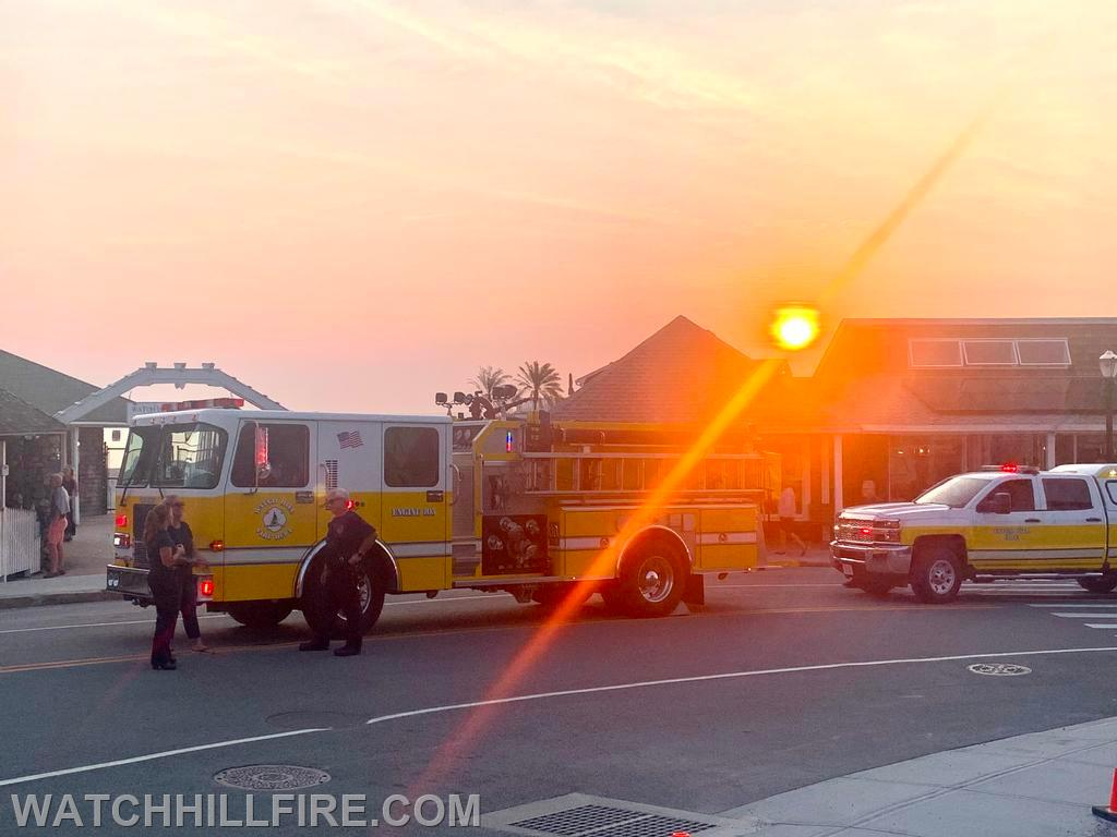The sun sets behind Engine 103 and Squad 100 at the last stop of the parade on Bay Street in Watch Hill
