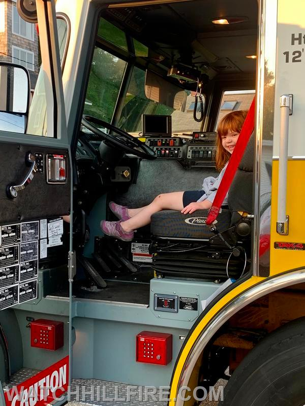 A child has their pictures taken while exploring Ladder 104 at the second stop of the parade in Weekapaug