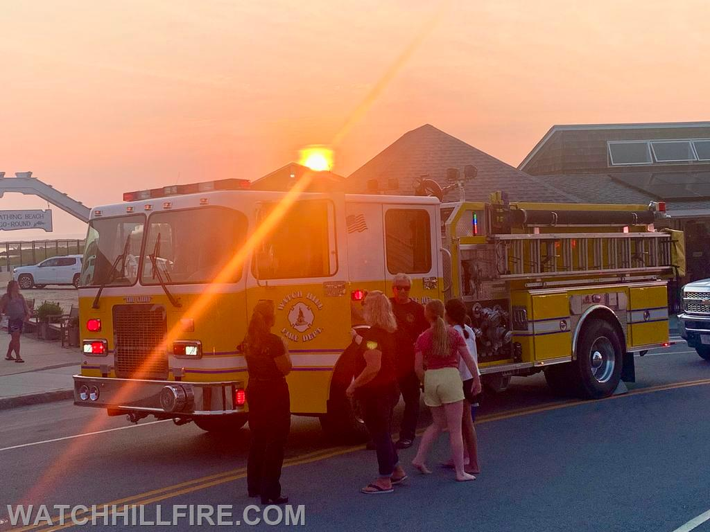 The sun sets behind Engine 103 at the last stop of the parade on Bay Street in Watch Hill