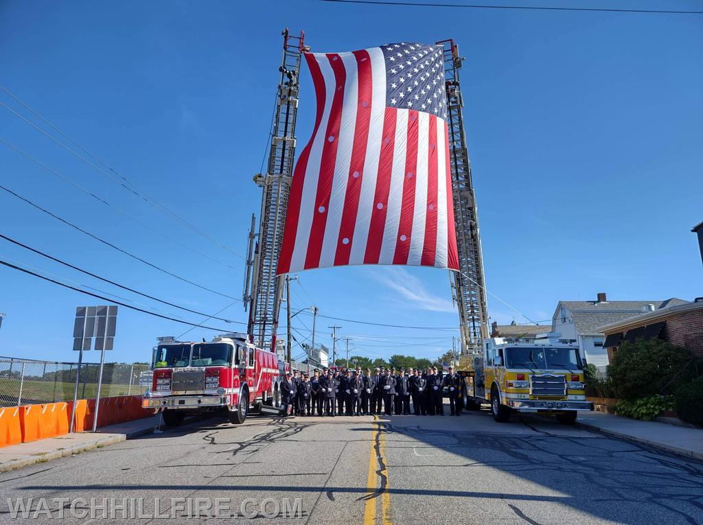 Firefighters Gather Under The Flag Between Watch Hill Ladder 104 and Westerly Ladder  1